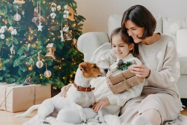 Szczęśliwa młoda kobieta obejmuje małą córeczkę, trzyma świąteczny prezent, czeka na ferie zimowe, bawi się z rodowodowym szczeniakiem