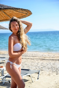 Szczęśliwa młoda kobieta odpoczywa na plaży w asprovalta, grecja