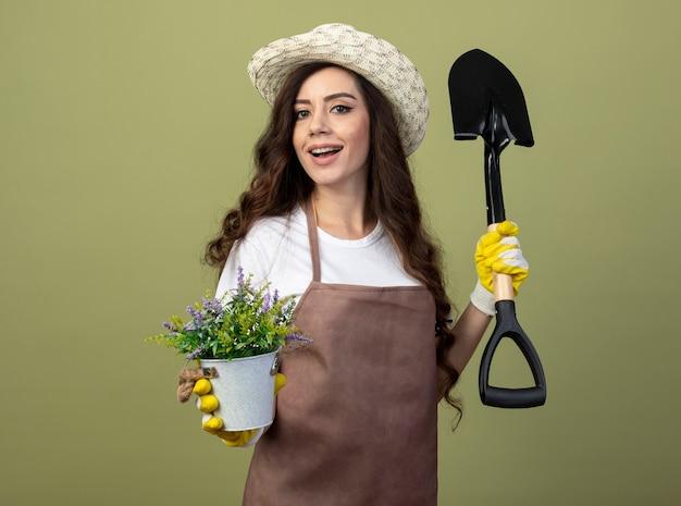 Szczęśliwa młoda kobieta ogrodnik w mundurze na sobie kapelusz ogrodniczy i rękawiczki trzyma łopatę i doniczkę na białym tle na oliwkowej ścianie