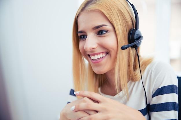 Szczęśliwa młoda kobieta operator w słuchawkach