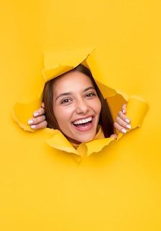 Szczęśliwa młoda kobieta patrząc na kamery i śmiejąc się, łzawienie dziury w jasny żółty papier