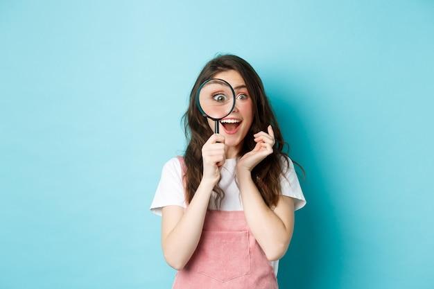 Szczęśliwa młoda kobieta patrząca przez szkło powiększające z podekscytowaną twarzą, znalazła lub szukała czegoś, stojąc na niebieskim tle