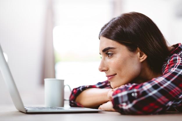 Szczęśliwa młoda kobieta patrzeje laptop