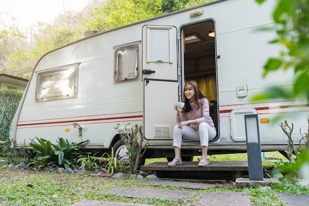 Szczęśliwa młoda kobieta picia kawy przy drzwiach kampera rv van samochód kempingowy