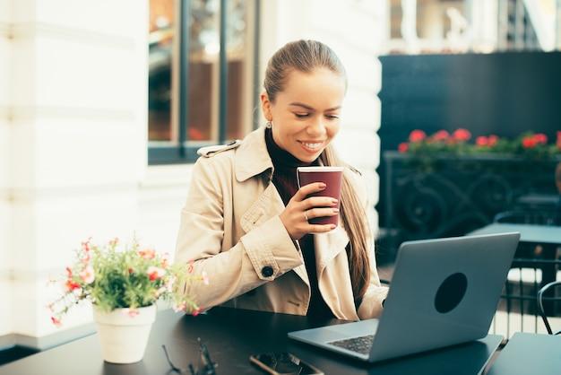 Szczęśliwa młoda kobieta pije cappuccino i patrząc na laptopa siedząc w kawiarni na świeżym powietrzu