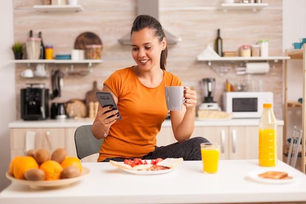 Szczęśliwa młoda kobieta pije filiżankę kawy i używa telefonu do czytania wiadomości