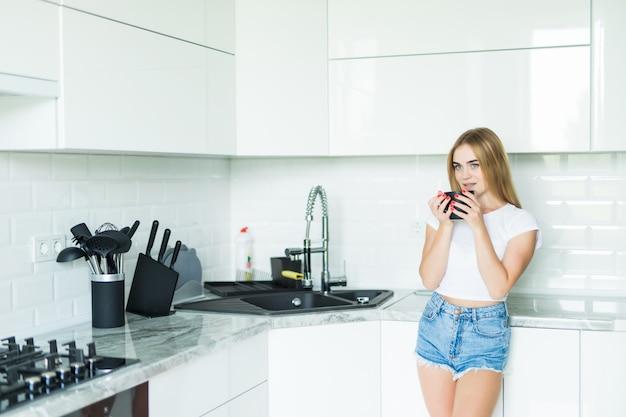 Szczęśliwa młoda kobieta pije herbaty w kuchni w domu
