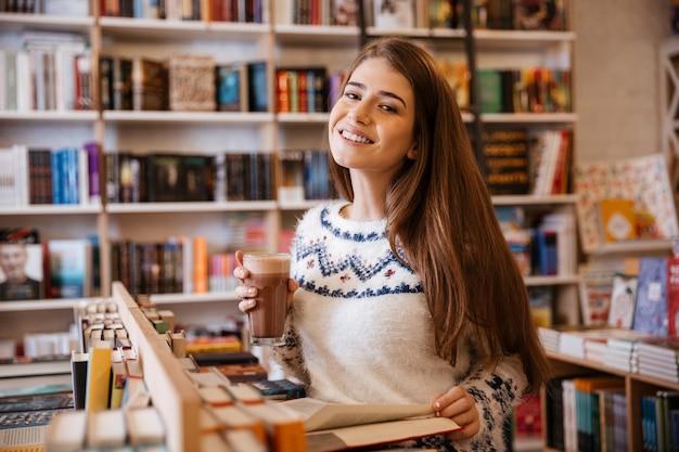 Szczęśliwa młoda kobieta pije kawę i czyta boo w pomieszczeniu