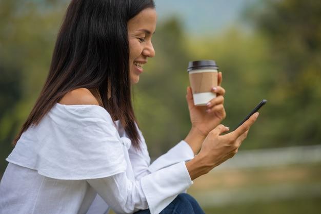 Szczęśliwa młoda kobieta pije kawę i używa smartphone