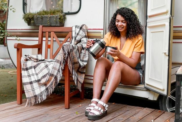 Szczęśliwa młoda kobieta pije kawę na ganku