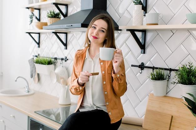 Szczęśliwa młoda kobieta pije kawę podczas gdy siedzący przy kuchnią w domu w ranku