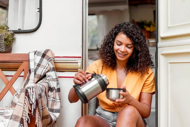 Szczęśliwa młoda kobieta pije kawę