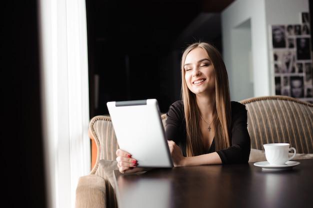 Szczęśliwa młoda kobieta pije kawową herbatę i używa pastylka komputer w sklep z kawą.