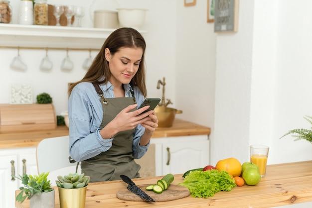 Szczęśliwa młoda kobieta pije sok pomarańczowy i przegląda przepisy kulinarne w swoim smartfonie. sałatka wegańska.