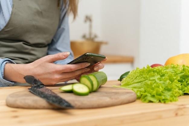 Szczęśliwa młoda kobieta pije sok pomarańczowy, przeglądając sieci społecznościowe na swoim smartfonie podczas gotowania. ścieśniać.