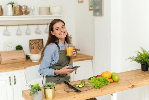 Szczęśliwa młoda kobieta pije sok pomarańczowy, przeglądając sieci społecznościowe na swoim smartfonie podczas gotowania.