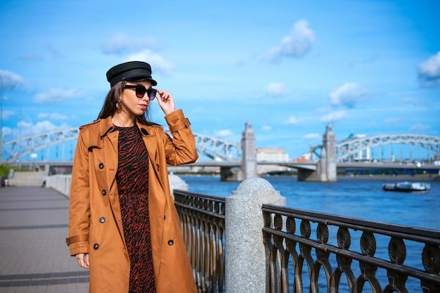 Szczęśliwa młoda kobieta pochodzenia kaukaskiego w jasnobrązowym płaszczu i czarnej czapce pozuje na nasypie