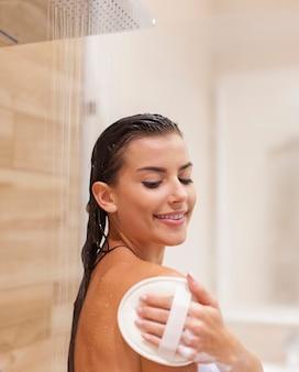 Szczęśliwa młoda kobieta pod prysznicem