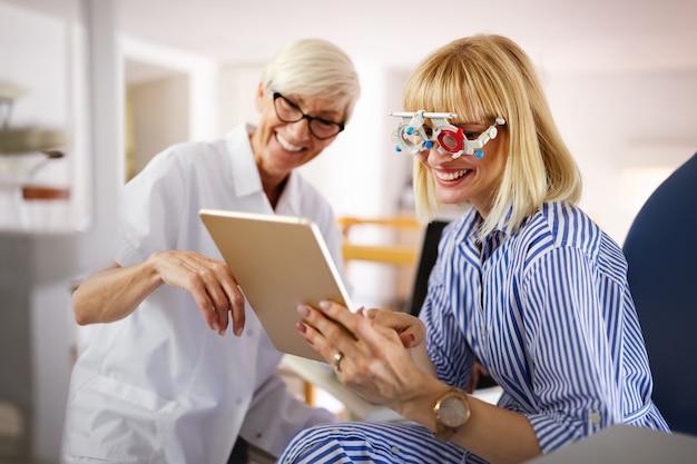 Szczęśliwa młoda kobieta podczas badania wzroku w klinice okulistycznej