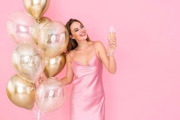 Szczęśliwa młoda kobieta podnosi kieliszek szampana trzyma wiele balonów powietrznych przybyłych na imprezę