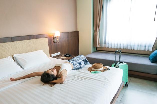 Szczęśliwa młoda kobieta podróżnik azjatyckich zrelaksować się na łóżku z kapeluszem i maską medyczną na łóżku w pokoju hotelowym