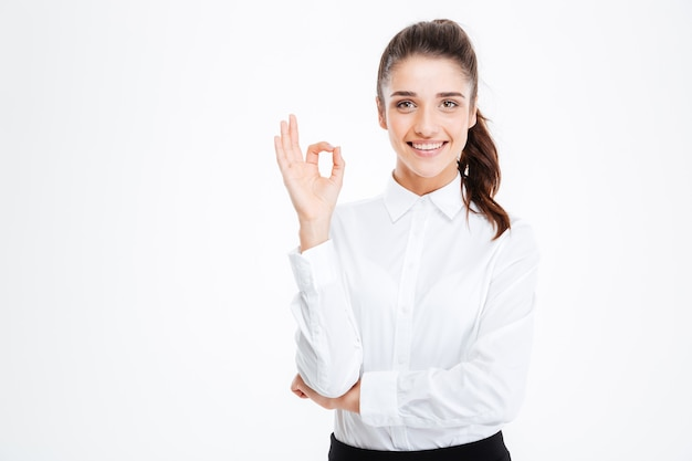 Szczęśliwa młoda kobieta pokazując znak ok na białej ścianie