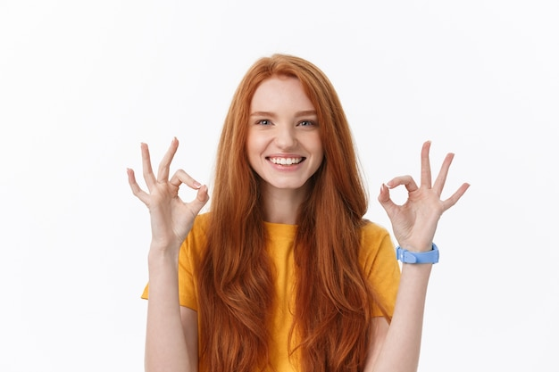 Szczęśliwa młoda kobieta pokazując znak ok palcami mrugając