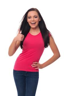 Szczęśliwa młoda kobieta pokazuje aprobaty znak