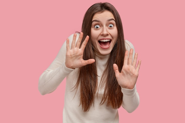 Szczęśliwa młoda kobieta pokazuje dłonie w ochronnym geście, jest zdumiona, pod wrażeniem ekscytujących wiadomości, ma szeroko otwarte oczy