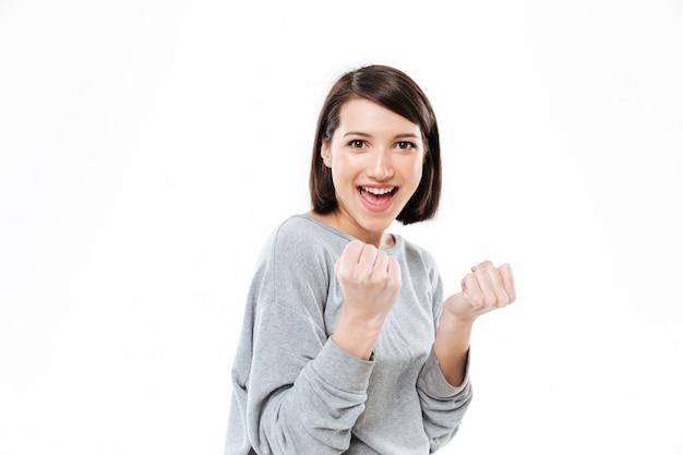 Szczęśliwa młoda kobieta pokazuje pięści i