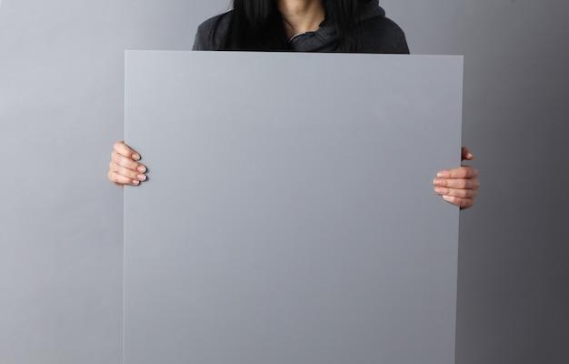 Szczęśliwa młoda kobieta pokazuje plakat i wystawia