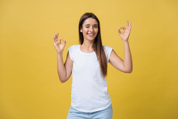 Szczęśliwa młoda kobieta pokazuje znak ok palcami i mruga na białym tle na żółtym tle