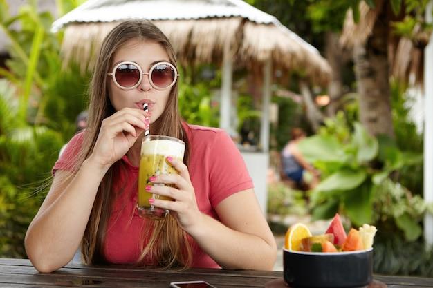Szczęśliwa młoda kobieta popijając świeżego drinka na wakacjach. atrakcyjna kobieta rasy kaukaskiej w modnych okrągłych odcieniach pije koktajl bezalkoholowy