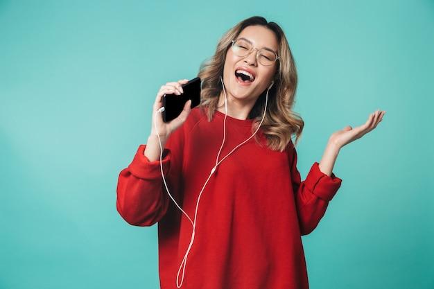 Szczęśliwa młoda kobieta pozuje na białym tle nad niebieską ścianą, słuchając muzyki za pomocą słuchawek za pomocą telefonu komórkowego