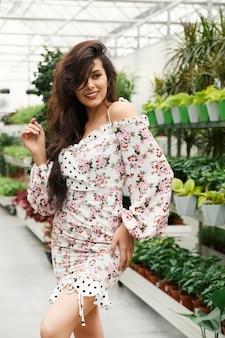 Szczęśliwa młoda kobieta pozuje w pobliżu pięknych zielonych roślin