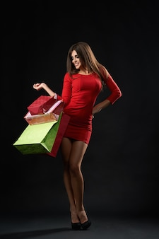 Szczęśliwa młoda kobieta pozuje z torba na zakupy
