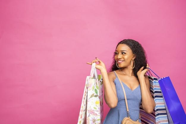 Szczęśliwa młoda kobieta pozuje z torbami na zakupy na różowej ścianie