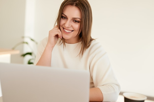 Szczęśliwa młoda kobieta pracuje na laptopie w kawiarni