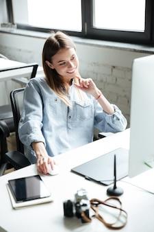 Szczęśliwa młoda kobieta pracuje w biurze przy użyciu komputera.