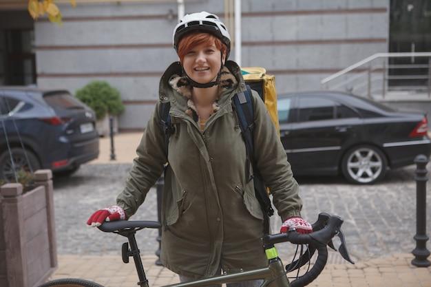 Szczęśliwa młoda kobieta pracuje w firmie kurierskiej jako kurier stojący z jej rowerem na zewnątrz