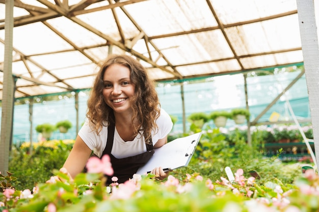 Szczęśliwa młoda kobieta pracuje w szklarni
