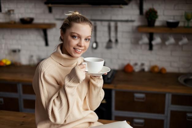 Szczęśliwa młoda kobieta przebywa w przytulnej domowej atmosferze, siedzi przy kuchennym stole i trzyma w dłoniach filiżankę kawy. wysokiej jakości zdjęcie
