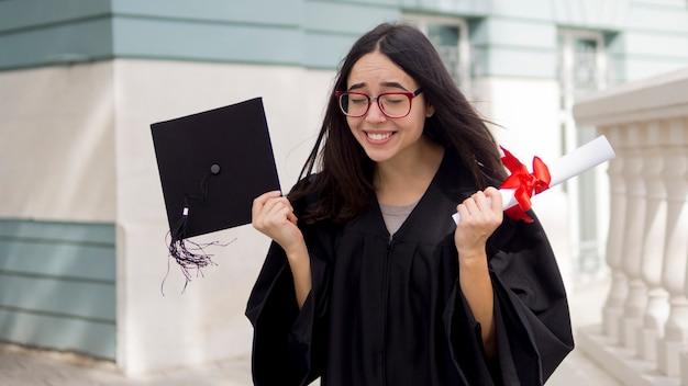 Szczęśliwa młoda kobieta przy ceremonią ukończenia szkoły