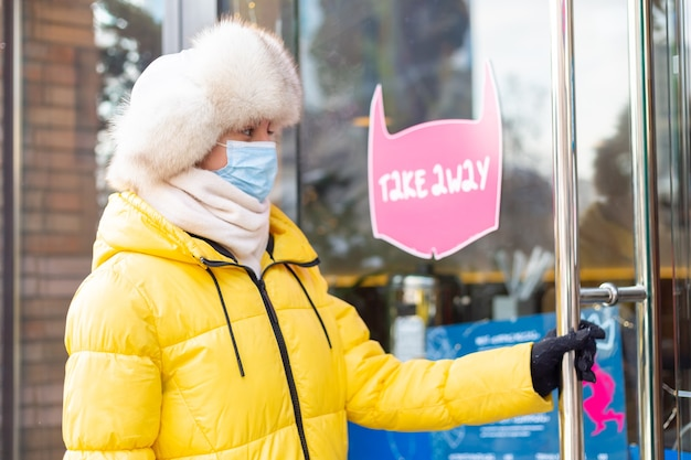 Szczęśliwa młoda kobieta przy drzwiach restauracji w mroźny zimowy dzień, napis, jedzenie na wynos.