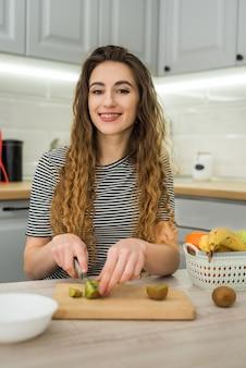 Szczęśliwa młoda kobieta przygotować robi sałatka owocowa do diety w kuchni, zdrowej żywności. pojęcie diety.