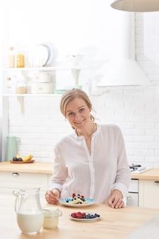 Szczęśliwa młoda kobieta przygotowywa smakowite przekąski przy kuchennym stołem w ranku świetle