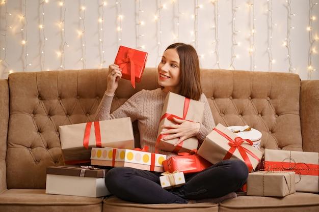 Szczęśliwa młoda kobieta przytulanie wielu obecnych pudełek siedzi skrzyżowanymi nogami na wielbłądzie kanapą z światłami