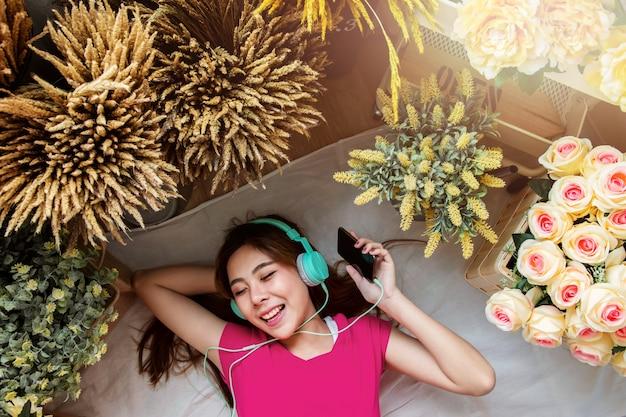 Szczęśliwa młoda kobieta r. na podłodze do słuchania muzyki za pośrednictwem inteligentnego telefonu