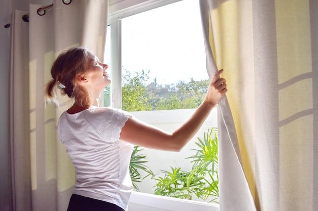 Szczęśliwa młoda kobieta rano otwiera zasłony