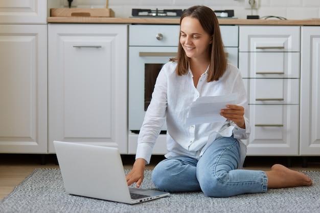 Szczęśliwa młoda kobieta rasy kaukaskiej siedzi na podłodze w kuchni, trzymając papierowy dokument lub list, sprawdzając rachunki krajowe, uśmiechając się, wykonując formalności lub studiując w domu.